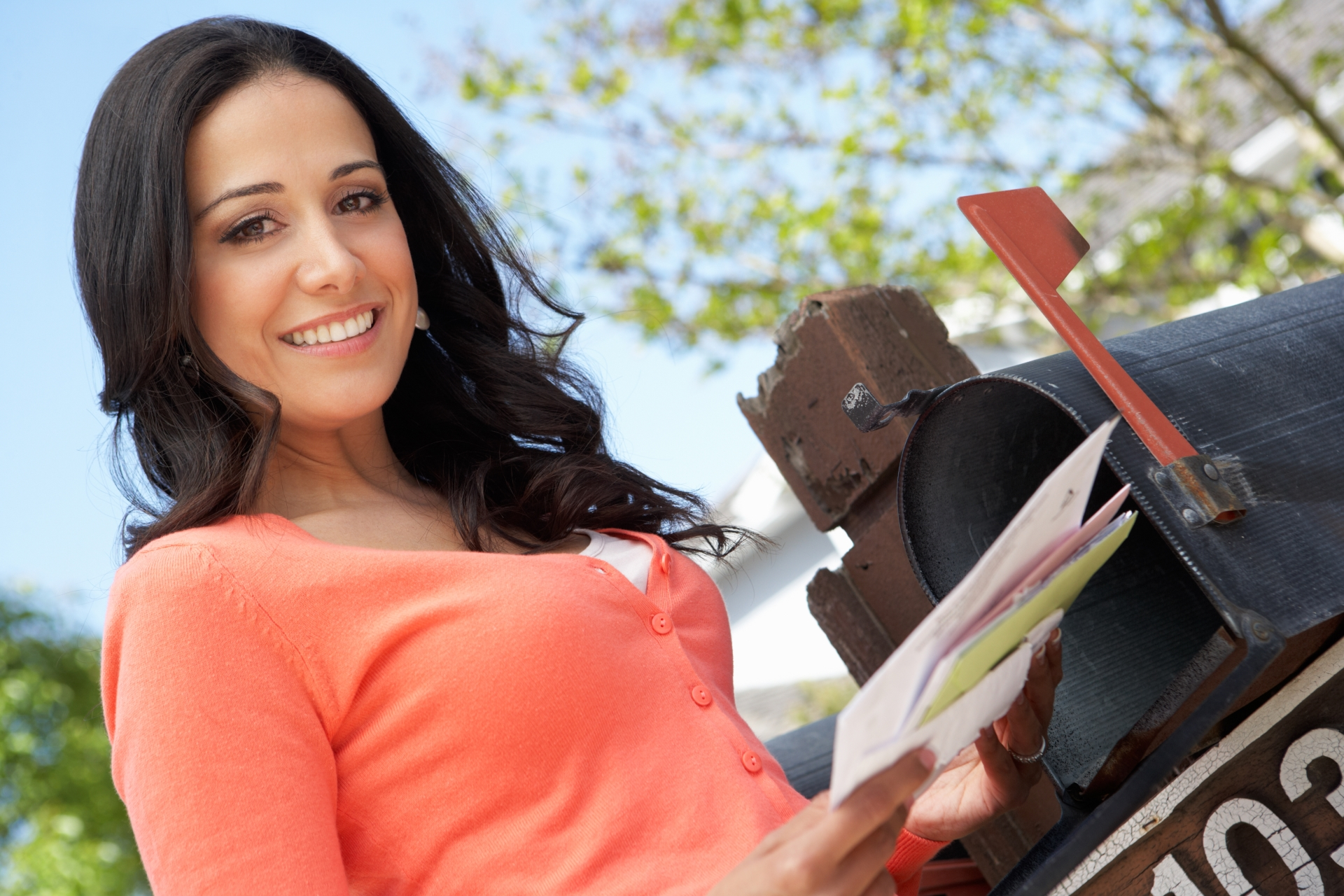 Woman smiling and looking into the camera while pulling various letters out of a black mailbox