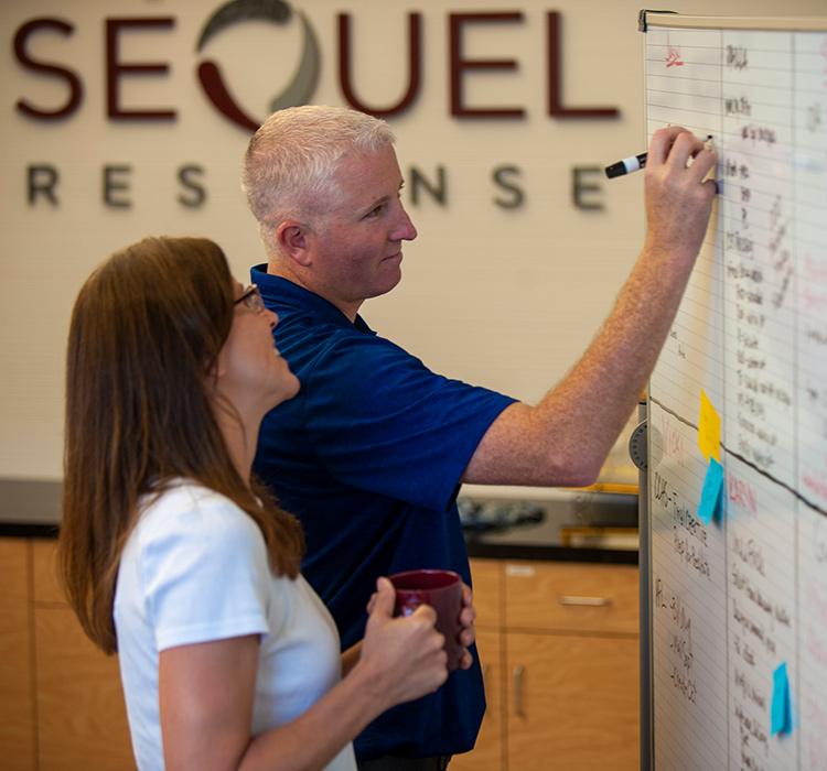 Man writing on SeQuel Response whiteboard while woman watches