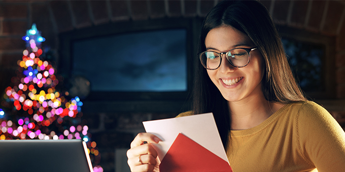 Woman opening a piece of holiday direct mail